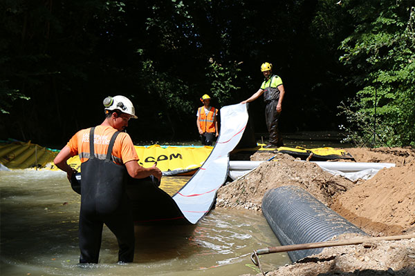 The flexible DP-3075 discharge hose, 450mm in diameter, is attached to the Water-Gate © weir. Then we roll out completely downstream before filling the water.